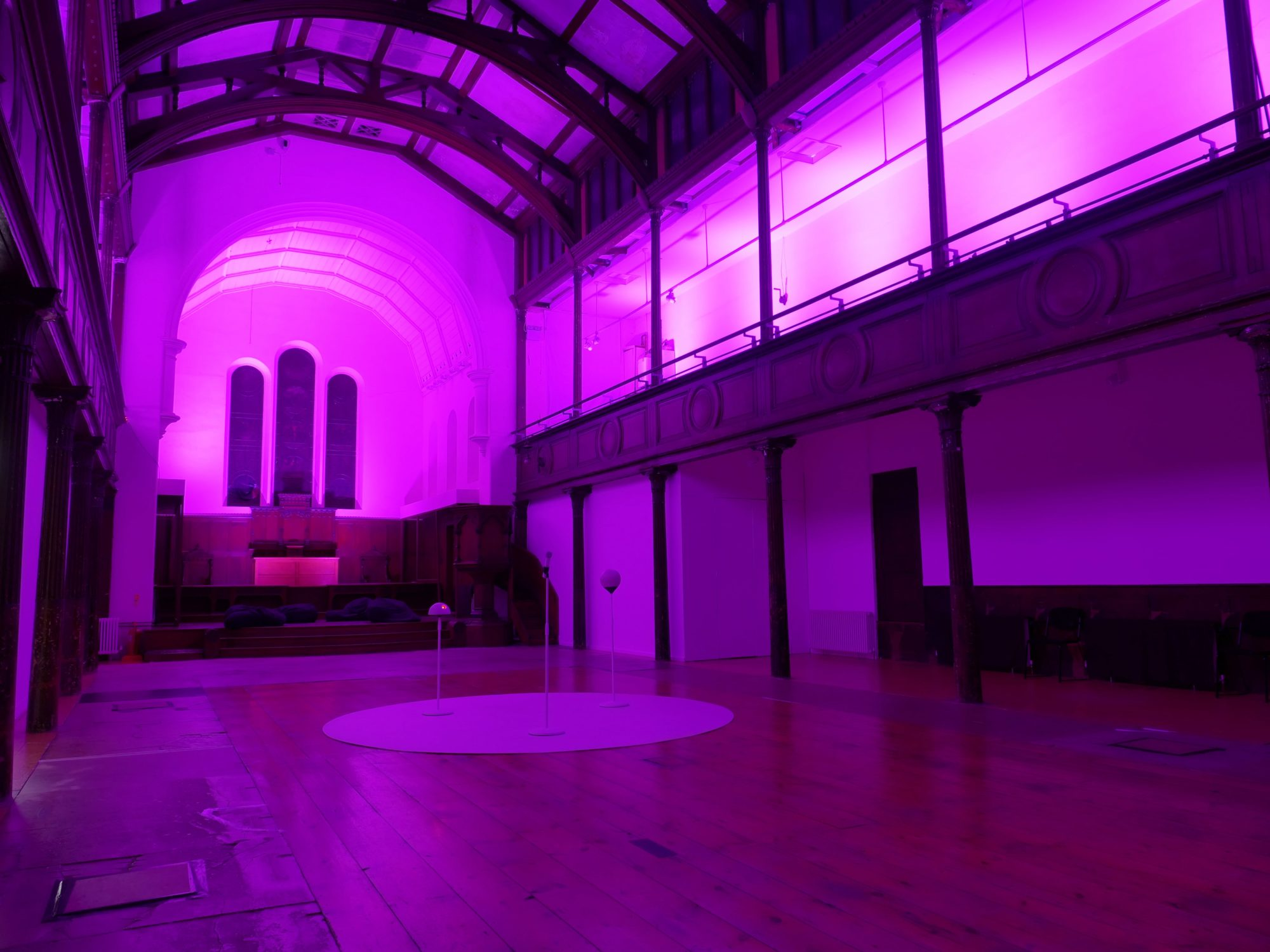 A large room bathed in pink light. A with circle in in the middle of the floor with three tall poles in the centre.