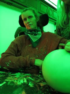 A women in a wheelchair is seated at a table covered in paint, wearing a jumper that is also covered in paint